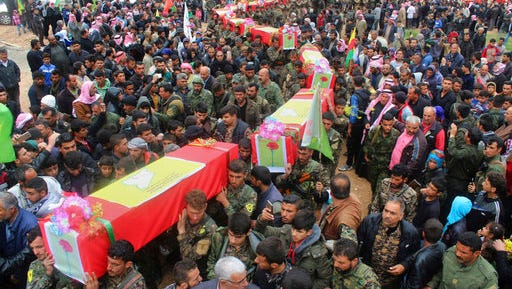 This photo provided by Hawar News Agency, a Kurdish-run news agency, which has been authenticated based on its contents and other AP reporting, shows fighters from the predominantly-Kurdish Syrian Democratic Forces carrying the coffins of their comrades, who were killed Tuesday by a misdirected airstrike by the U.S.-led coalition, during their funeral procession, in Tal al-Abyad, northeast Syria, Thursday, April 13, 2017. U.S. Central Command said coalition aircraft were given the wrong coordinates by their partner forces, the Syrian Democratic Forces, for a strike intended to target Islamic State militants south of their Tabqa stronghold.