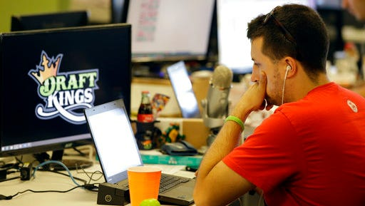FILE- In this Sept. 9, 2015, file photo Devlin D'Zmura, a tending news manager at DraftKings, a daily fantasy sports company, works on his laptop at the company's offices in Boston. The daily fantasy sports industry has contracted starkly since questions about the legality of online games offered by companies sparked court and legislative battles across the U.S. last year.