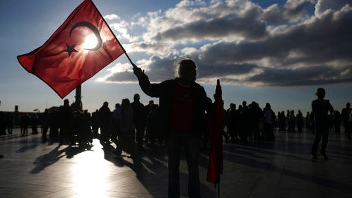 A supporter of the 'no' vote, holds a Turkish flag during a protest regarding Sunday's referendum outcome, on the Aegean Sea city of Izmir, Turkey, Tuesday, April 18, 2017.  Turkey's main opposition party has filed a formal request seeking Sunday's referendum to be annulled because of alleged voting irregularities.