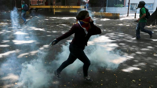 """A demonstrator throws back a tear gas canister during clashes with security forces at a protest in Caracas, Venezuela, Wednesday, April 19, 2017. Venezuelan National Guard members are deploying tear gas on an opposition march in western Caracas in an effort to disperse demonstrators. Opponents of President Nicolas Maduro called on Venezuelans to take to the streets on Wednesday for what they dubbed the """"mother of all marches"""" against the embattled socialist leader."""