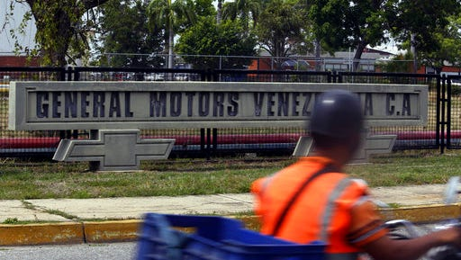 A motorcyclist rides past the General Motors' plant in Valencia, Venezuela, Thursday, April 20, 2017. The company announced that it was shuttering operations in the country after authorities seized the factory on Wednesday, April 19. General Motors' announcement comes as Venezuela's opposition looks to keep up pressure on President Nicolas Maduro, taking to the streets again Thursday after three people were killed and hundreds arrested in the biggest anti-government demonstrations in years.