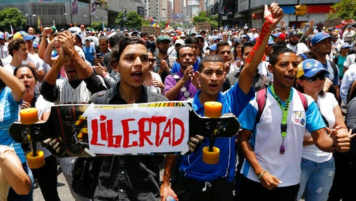 Opponents of President Nicolas Maduro march in Caracas, Venezuela, Thursday, April 20, 2017. Tens of thousands of protesters flooded the streets again Thursday, one day after three people were killed and hundreds arrested in the biggest anti-government demonstrations in years.