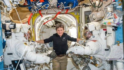 FILE - In this Jan. 13, 2017 file photo made available by NASA, astronaut Peggy Whitson, center, floats inside the Quest airlock of the International Space Station with Thomas Pesquet, left, and Shane Kimbrough before their spacewalk. Early Monday, April 24, 2017, the International Space Station commander surpassed the 534-day, two-hour-and-48-minute record set last year by Jeffrey Williams for most accumulated time in orbit by an American.  Whitson already was the world's most experienced spacewoman and female spacewalker and, at age 57, the oldest woman ever in space.