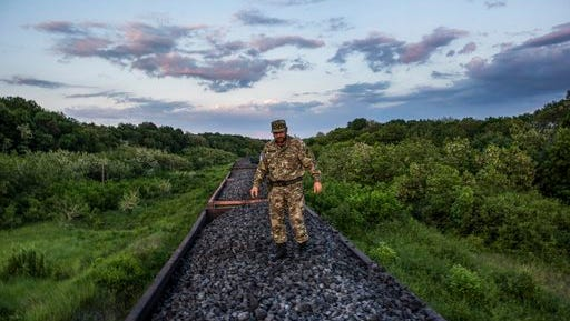 FILE - In this Tuesday, June 2, 2015 file photo, Mykola Tsukur, deputy commander of the volunteer Tornado battalion, stands atop a train carrying coking coal from the rebel-held parts of the Luhansk region into the government-controlled area in Orekhove, Ukraine. In a move that further cements Russia's control over parts of eastern Ukraine, Russian officials announced Tuesday, April 25, 2017 that they will begin supplying electricity to separatist-controlled areas in eastern Ukraine after the Ukrainian government cut the power off because of millions in unpaid bills.
