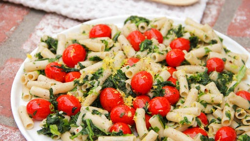 This April 2017 photo shows penne with tomatoes, garlic, lemon and spinach in Coronado, Calif. This dish is from a recipe by Melissa d'Arabian.