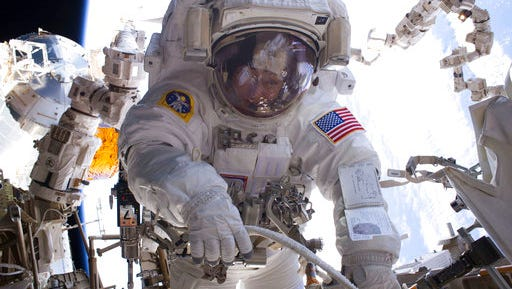 In this Jan. 6, 2017 photo made available by NASA, astronaut Peggy Whitson performs a spacewalk during Expedition 50 aboard the International Space Station. According to a report released Wednesday, April 26, 2017, NASA is managing a variety of design and health risks associated with the spacewalking suits used by astronauts aboard the International Space Station. The suits were developed more than 40 years ago and intended for only 15 years' use.