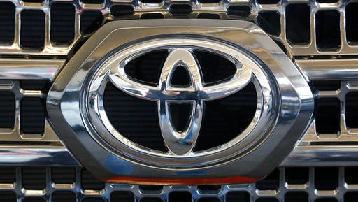 FILE - This Thursday, Feb. 11, 2016, file photo shows the Toyota logo on the grill of a 2016 Toyota Tacoma on display at the Pittsburgh International Auto Show, in Pittsburgh. Toyota is recalling about 250,000 small pickup trucks mainly in North America because the rear wheels have the potential to lock up, causing drivers to lose control. The recall covers certain Tacoma trucks from 2016 and 2017.