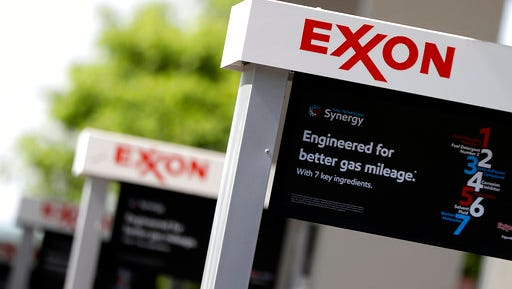 This April 25, 2017, photo, shows Exxon service station signs in Nashville, Tenn. Exxon Mobile Corp. reports earnings on Friday, April 28, 2017.