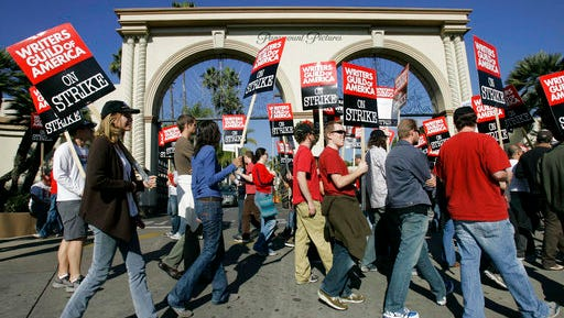FILE - In this Dec. 13, 2007, file photo, striking writers walk the picket line outside Paramount Studiosin Los Angeles. The clock is ticking on negotiations between television and film writers and producers before their contract expires. A strike could begin Tuesday, May 2, 2017, forcing writers to begin picketing. The previous writers' strike lasted 100 days in 2007-08 and was costly to the businesses that serve Hollywood and to consumers expecting to be entertained.