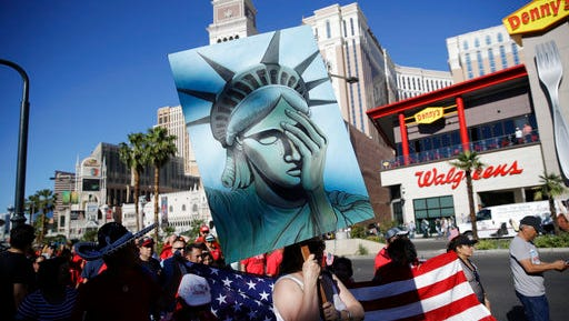 People walk along the Las Vegas Strip during a May Day march, Monday, May 1, 2017, in Las Vegas. Union members and activists marched along and near the Las Vegas Strip to highlight immigration issues and push back against Trump administration policies.