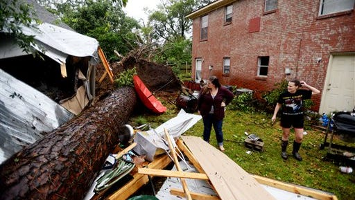 Brittany Garner, right, shows Toshia Laing the tree that fell in her backyard during the storm Monday, Oct. 13, 2014, in Monroe, La.