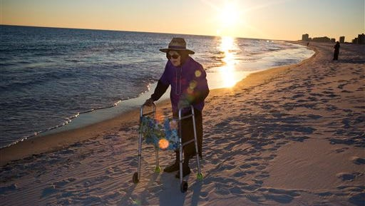 """Ruby Holt, a 100-year-old Tennessee native, reflects as she sees the ocean for the first time in her life Wednesday in Orange Beach, Ala. The Brookdale Senior Living and Wish of a Lifetime organizations both provide Holt a wish of her choice. She chose to see the ocean for the first time. """"It's cold,"""" Holt said after dipping her feet into the ocean for the first time."""