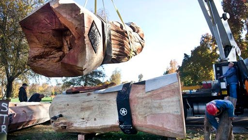 Crews begin erecting the world's tallest wooden nutcracker for the Umpqua Valley Festival of Lights, Monday Nov. 17, 2014 in Roseburg, Ore.  The 41-foot nutcracker was carved with chainsaws by Toby Johnson. (AP Photos/The News-Review, Katie Alaimo)