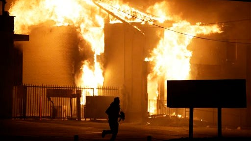 A man runs away from the burning storage facility after  the announcement of the grand jury decision Monday, Nov. 24, 2014, in Ferguson, Mo. A grand jury has decided not to indict Ferguson police officer Darren Wilson in the death of Michael Brown, the unarmed, black 18-year-old whose fatal shooting sparked sometimes violent protests. (AP Photo/David Goldman)