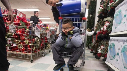 Dylan Morales pouts while shopping with his father Rigoberto, at Kmart on 34th Street, Thursday, Nov. 27, 2014, in New York. Millions of customers are expected to shop on Thanksgiving Day as many retailers remain open on a day traditionally reserved for spending time with family. (AP Photo/John Minchillo)