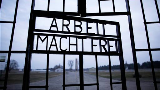 FILE - This Jan. 27, 2012, file photo shows the words 'Arbeit Macht Frei' (Work Sets You Free) at the main entrance of the Sachsenhausen Nazi concentration camp on the international Holocaust remembrance day in Oranienburg, Germany. An Associated Press investigation found dozens of suspected Nazi war criminals and SS guards collected millions of dollars in Social Security payments after being forced out of the United States.  (AP Photo/Markus Schreiber, File)