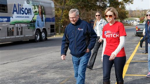 Senate Minority Leader Mitch McConnell, R-Ky., accompanied by a staff member, walks past the campaign bus of his Democratic challenger, Alison Lundergan Grimes, at the start at the Veterans Day Parade in Madisonville, Ky., Sunday, Nov. 2, 2014. McConnell, a 30-year incumbent, would ascend to majority leader if he holds his seat and Republicans take control of the Senate.  (AP Photo/J. Scott Applewhite)