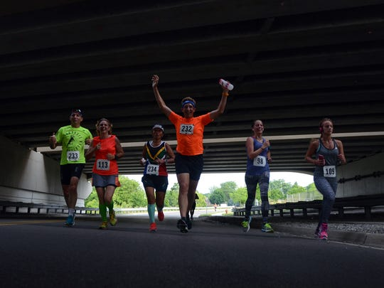A group of runners make their way along Scott Avenue under the I-69 Black River overpass Sunday, June 26, during the Blue Water Half Marathon in Port Huron.