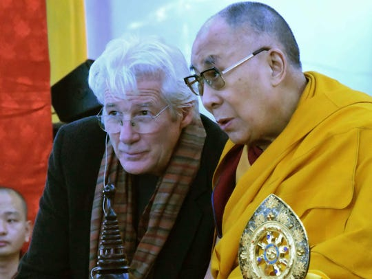 Tibetan spiritual leader, the Dalai Lama, right,  speaks