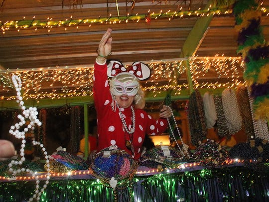 A masked Mardi Gras reveler throws beads from a float in the Krewe of Janus parade in 2015.