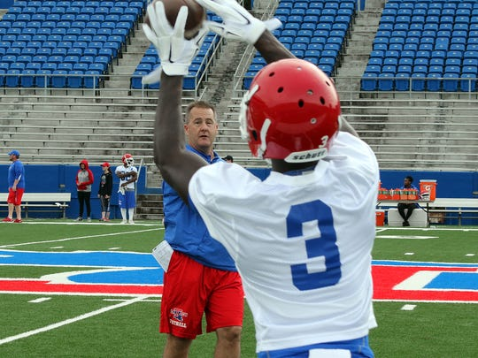 Louisiana Tech offensive coordinator/wide receivers coach Todd Fitch throws a pass to Tulane transfer Tedd Veal in Friday's practice.