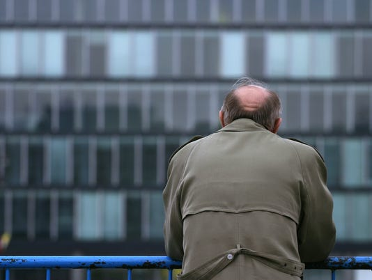 Bald man in brown standing alone against a blue railing