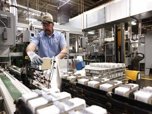 A worker makes a battery at a JCI plant