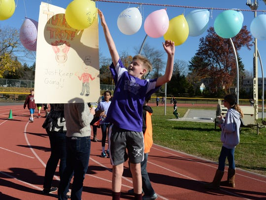 Ridgewood, NJ 11/18/16  Benjamin Franklin Middle School student Dan Weaver jumps for the balloon as he completes his 40th lap around the track.   Benjamin Franklin MS pledged to donate one turkey for every 50 laps run by all participants.