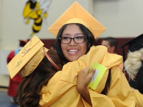 Alejandra Cano (back to camera) and Luz Martinez hug before lining up for the procession before the Oxnard High School commencement ceremony Friday. The school had 654 graduates.