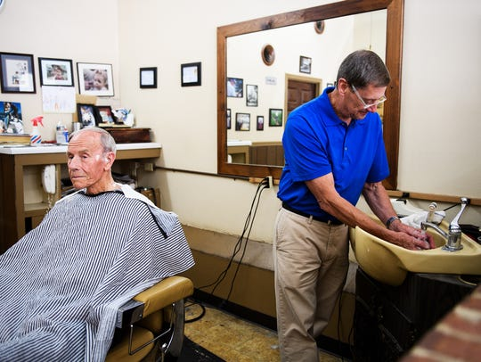 Mike Bullock of Bullocks Barber Shop washes his hands