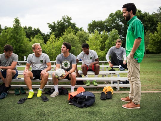 Richard Carrizales (far right) and his brother Marco (holding soccer ball) speak to Greenville FC players before a practice on Friday, June 22, 2018.