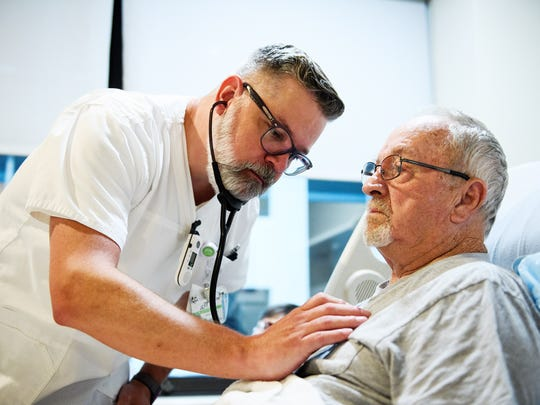 Jeffery Everett, staff nurse at Greenville Memorial Hospital, meets with patient Lester Waldrop on Friday, July 6, 2018.