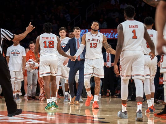 St. John's Marvin Clark II (13) and Bryan Trimble Jr., (12) celebrate during a time out in the second half of an NCAA college basketball game against Duke at Madison Square Garden in New York, Saturday, Feb. 3, 2018. St. John's defeated No. 4 Duke 81-77. (AP Photo/Andres Kudacki)