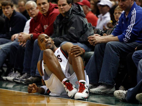Bucks guard Michael Redd falls to the ground and grabs