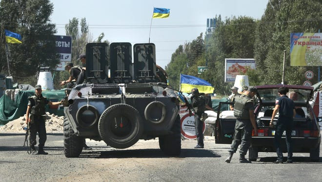 Ukrainian soldiers secure a checkpoint in the town of Mariupol, eastern Ukraine on Aug. 27, 2014.