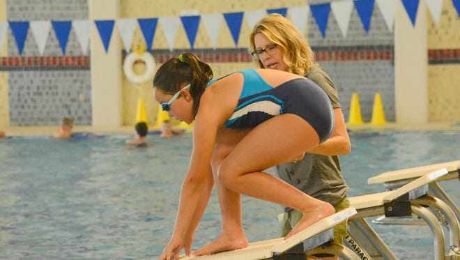 Carlsbad swim coach Michelle White works with Regan Chavez, 9, on starts during the annual CHS swim team camp on Monday.