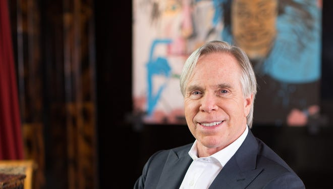 """Designer Tommy Hilfiger, at home in New York at the Plaza Hotel Residences in front of a painting by Jean-Michel Basquiat, titled """"Dos Cabezas"""" on Feb. 4, 2014."""