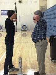 Simon Kenton head coach Glenn Keith gives instructions during Simon Kenton archery practice at Piner Elementary, April 19, 2017.