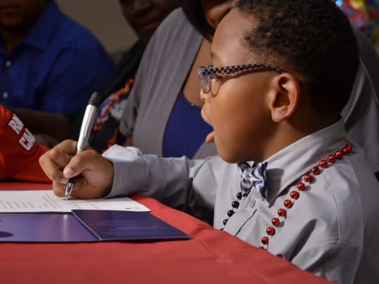 Tay'Shawn Landry, 10, signs to become an honorary Ragin' Cajun.