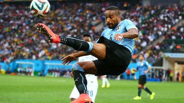 Uruguay midfielder Alvaro Pereira leaps to control the ball in the first half against England during the 2014 World Cup at Arena Corinthians. Uruguay defeated England 2-1.