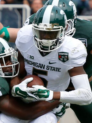 Michigan State receiver DeAnthony Arnett, right, is brought down during the spring game Saturday, April 25, 2015, in East Lansing.
