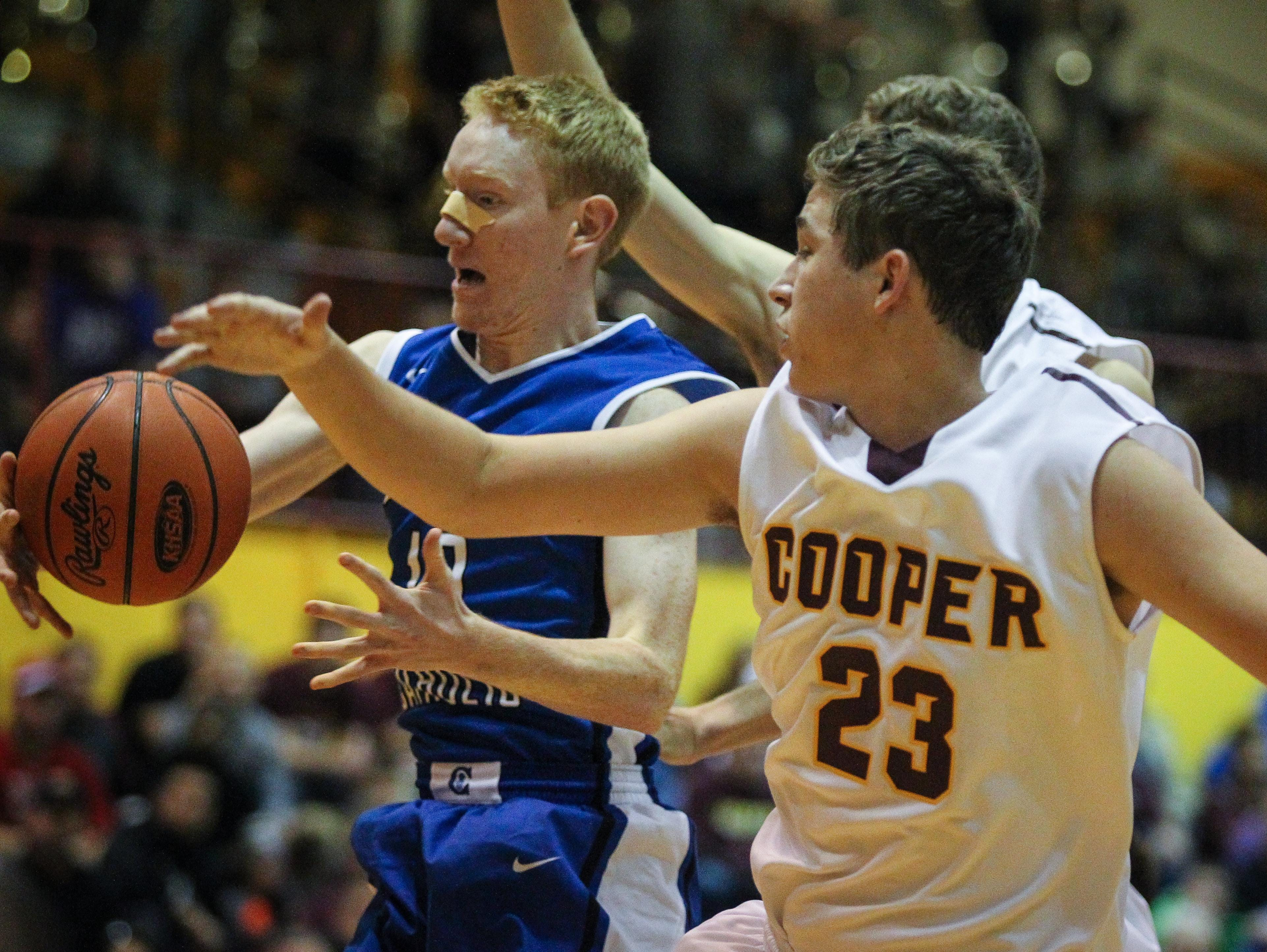 Covington Catholic's Ryan Massie rebounds a missed free throw in front of Cooper's Trevor Rohlman during the first half of their game Wednesday.