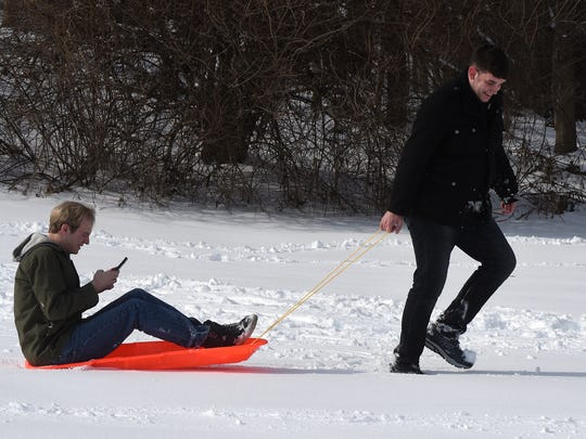 Brett Crisp (right) pulls Alex Barber (left) on a sled as they leave Geller Park after a sledding excursion on Wednesday, Feb. 7, 2018. Licking County received about four inches of snow resulting in a level two snow emergency in the morning.