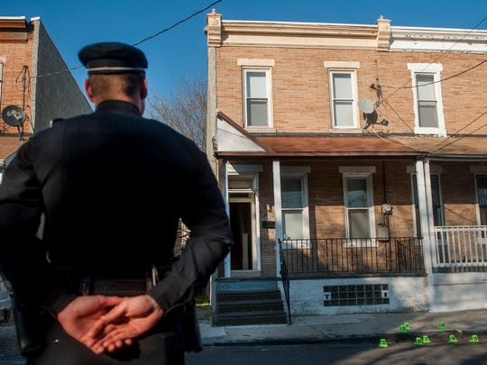 A Camden County police officer stands in front of a home on the 500 block of South 8th Street in Camden where two men were found dead Thursday morning.  04.14.16