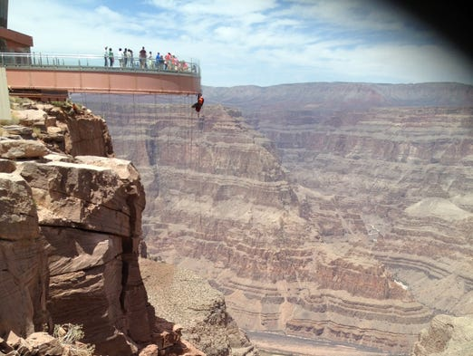 Visitors enjoy the Grand Canyon Skywalk while a worker on cleaning duty dangles below.
