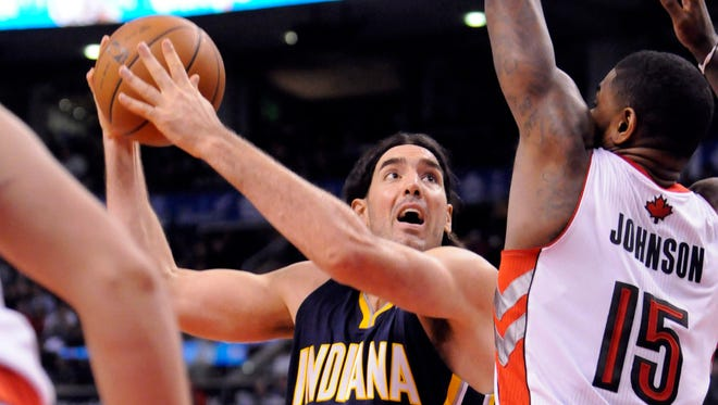 Indiana Pacers power forward Luis Scola (4) takes a shot with Toronto Raptors power forward Amir Johnson (15) defending during the fourth quarter of a game at the Air Canada Centre. Toronto won the game  95-82.