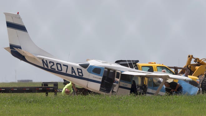 Airport workers inspect a small plane as they prepare it to be towed after a hard landing that sent one perons to the hospital Friday, June 27, 2014