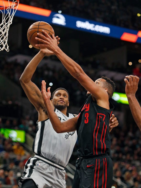 Portland Trail Blazers shooting guard C.J. McCollum (3) has his shot blocked by San Antonio Spurs forward Rudy Gay (22) during the first half of an NBA basketball game Saturday, April 7, 2018, in San Antonio. (AP Photo/Ronald Cortes)