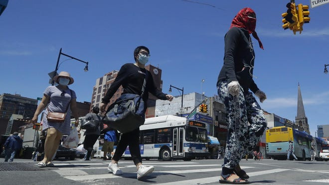 Pedestrians wear face coverings and protective masks as they cross Mains street Patrons enter a cosmetic store Monday, June 8, 2020, in the Flushing section of the Queens borough of New York. After three bleak months, New York City will try to turn a page when it begins reopening Monday after getting hit first by the coronavirus, then an outpouring of rage over racism and police brutality.