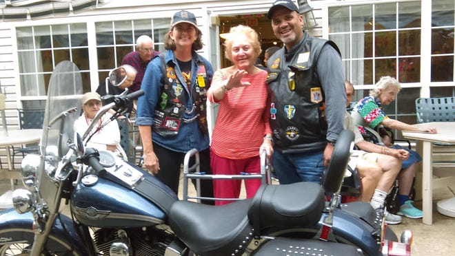 Jean Gailey waves to friends as she looks over the motorcycles.